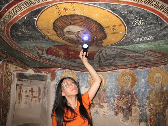 The researchers analyzed some of the paintings on site using various techniques, including infrared, ultraviolet and X-ray fluorescence imaging. Here, UCLA archaeologist Ioanna Kakoulli examines a painting in the monastery under UV light. Credit: Ioanna Kakoulli, UCLA